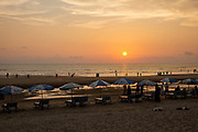 A row of sun-lounger beds and umbrellas at sunset on Laboni Beach looking out to the Bay of Bengal near in Cox Bazar, Chittagong Division, Bangladesh, Asia.  People stand around the sun-beds and others with two sleeping dogs, other people walk along the shoreline. This is part of the coastline which is claimed to be the longest natural sea sandy beach in the world, running 120 kilometers.  (photo by Andrew Aitchison / In pictures via Getty Images)