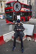Street scene on Oxford Street in central London, UK. Britiains busiest shopping district. Sitting on the street corner texting under a sign for a road crossing.