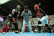 Two 2 male fighters and referee starting a bout. Lucha Libre wrestling origniated in Mexico, but is popular in other latin Amercian countries, including in La Paz / El Alto, Bolivia. Male and female fighters participate in the theatrical staged fights to an adoring crowd of locals and foreigners alike.