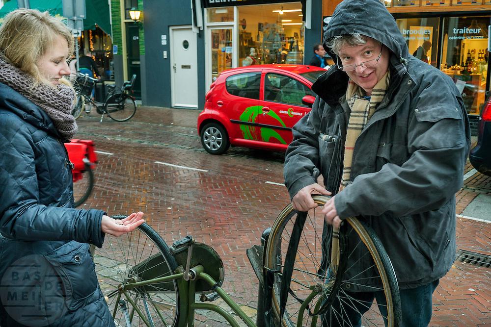vader helpt dochter met band plakken in de regen. dochter kijkt toe. Utrecht. Man kijkt in camera.