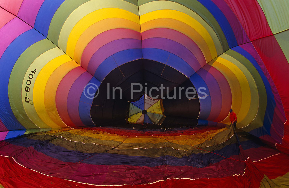 A hot air balloon is partially inflated before flight at Longleat Estate, Warminster, England. Using firstly cold air from a gas-powered fan, before its propane burners are used for final inflation, one of the ground crew assists in the process by pulling at the fragile synthetic material so that the volume within the whole 'envelope' can fill without damage and it's spectrum arc of colours are becoming rainbow-like. The hot air balloon is the oldest successful human-carrying flight technology. The first manned flight was made by Jean-François Pilâtre de Rozier and François Laurent d'Arlandes in a balloon created by the Montgolfier brothers in 1783. In today's sport balloons the envelope is generally made from nylon fabric and the mouth of the balloon (closest to the burner flame) is made from fire resistant material such as Nomex.