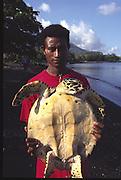 Papua New Guinea, Long Island, Islander with turtle, black sand beach<br />