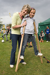 Grandmother helping her daughter to learn to use stilts at a Parklife summer activities event,