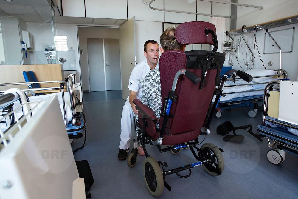 Nederland Rotterdam  31-08-2009 20090831 Foto: David Rozing .Serie over zorgsector, Ikazia Ziekenhuis Rotterdam. Afdeling neurologie, stroke unit, revalidatie  bejaarde man op zaal. Broeder praat met patient, na de  oefeningen om opnieuw te leren lopen. De patient heeft een beroerte gehad en daardoor is oa zijn ( grove ) motoriek aangetast, deels verlamd geraakt. rolstoel, wheelchair.  Revalidation old patient, nurse talks to patient who has suffered a stroke.  .Na een ernstige beroerte wordt u opgenomen in een gespecialiseerde afdeling of een afdeling intensieve zorgen van het ziekenhuis. Na de eerste 24 uur is het nodig om een aangepast revalidatieprogramma te starten. dat kan bestaan in wisselhoudingen en passieve bewegingen van de verlamde lichaamshelft.  .  ..Foto: David Rozing  ..Foto: David Rozing ..Holland, The Netherlands, dutch, Pays Bas, Europe, ronde doen, routine verpleegkundigen, verpleger, verplegers, verplegend, status., interactie patient verpleging, praatje maken met, tijd hebben voor, aandacht hebben voor geven,  hulp, helpen,, nursing, aansterken, handeling, handelingen,Holland, The Netherlands, dutch, Pays Bas, Europe, menselijk contact ,   oud, oude, op leeftijd, revalidatie, revalideren, revalidation, nursing,steun, steunen, warmte geven, helpen, hart onder de riem steken,aanmoedigen, moral support, blijk van affectie, steuntje in de rug,  steunbetuiging,onherkenbaar, onherkenbare, unrecognisable,copy space, ruimte voor tekst,  , mobiliteit, niet mobiel zijn, verlamd zijn, niet goed kunnen lopen, ,zorgverlener, zorgverleners,zorgverlening,ondersteunen, helpen te met,moral support, blijk van affectie, steuntje in de rug,  steunbetuiging, verpleger, verplegers, verplegend....Foto: David Rozin