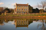 High House Farm farmhouse reflected in water of newly dug pond, Bawdsey, Suffolk, England