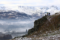 © Licensed to London News Pictures. 20/01/2019. Lake District, UK. People enjoy the view from the summit of Loughrigg Fell in the Lake District as the surrounding mountains are covered in snow and fog fills the valleys during cold weather. Photo credit : Tom Nicholson/LNP