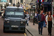 Shoppers walk past a reinforced RUC Land Rover Tangi vehicle in the city centre, on 7th June 1995, in Belfast, Northern Ireland, UK.