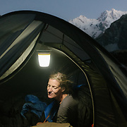 Woman in her tent at night, lit by camping light. Angel.