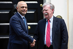 © Licensed to London News Pictures. 13/08/2019. London, UK. Chancellor of the Exchequer Said Javid (l) shakes the hand of the National Security Advisor of the United States John Bolton outside 11 Downing Street. Photo credit: George Cracknell Wright/LNP