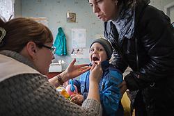 Dr Marina Shcherbakova examines Alexander, 3 yr 7 month, who has come with his mother Svetlana Mulik, 38, to the MSF mobile clinic in the Lugansk suburb of Bolshaya Vergunka.
