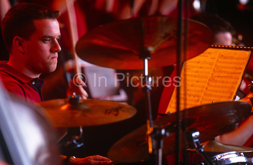 A drummer works hard during live performance in south London. With a sheet music score to refer to, the young man is a member of a London youth jazz orchestra, playing in front of a large crowd in Dulwich. With a keen sense of rhythm and tempo, he strikes his drums and cymbals with regular timing.