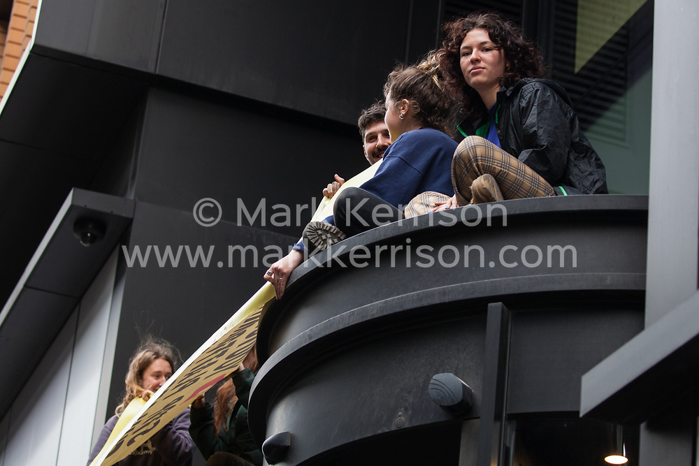 London, UK. 16 October, 2019. Climate activists from Extinction Rebellion's XR Youth defy the Metropolitan Police ban on Extinction Rebellion Autumn Uprising protests under Section 14 of the Public Order Act 1986 by protesting above the entrance to and outside the Kings Cross headquarters of US video-sharing website company YouTube against its role in 'enabling the spread of systematic disinformation on climate change and the ecological crisis'.