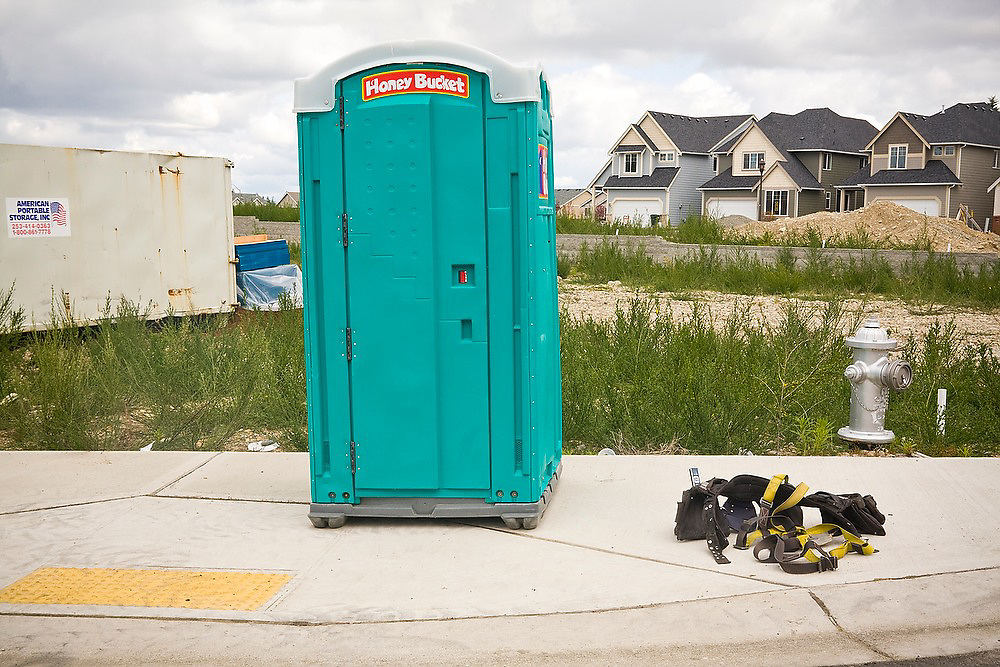 A construction worker's chest harness and carpenter tool belt sits in a pile besides a Honey Bucket portable toilet at a new housing development in Tacoma, Washington.