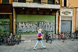 A woman walks past graphiti on a closed shop in the Via degli Orefici, Bologna, Italy<br /> <br /> (c) Andrew Wilson | Edinburgh Elite media