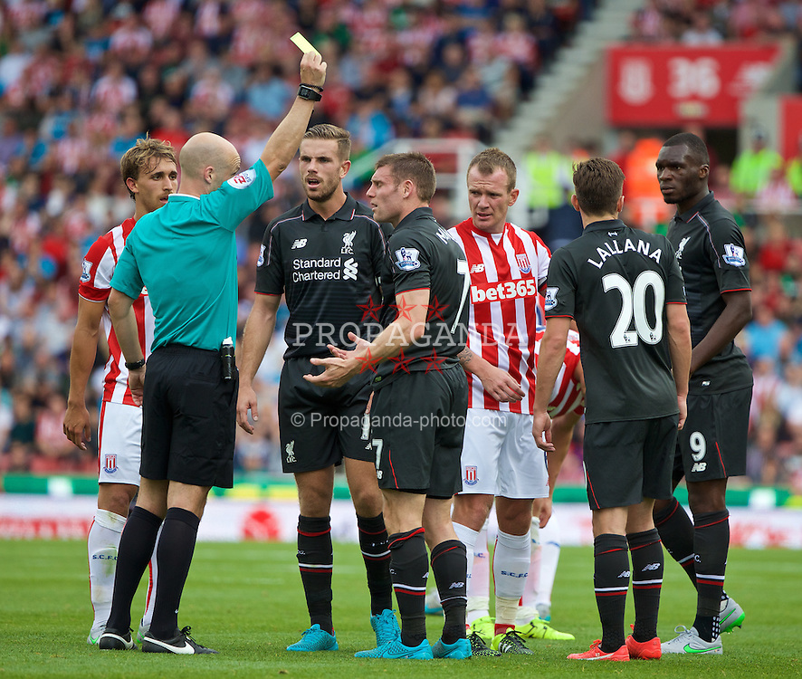 STOKE-ON-TRENT, ENGLAND - Sunday, August 9, 2015: Liverpool's James Milner is shown a yellow card by referee Anthony Taylor against Stoke City during the Premier League match at the Britannia Stadium. (Pic by David Rawcliffe/Propaganda)