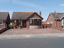 Modern detached bungalow with paved-over frontage for car parking.