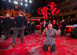 © Licensed to London News Pictures. 07/11/2015.  Royal Albert Hall, London, UK.  A man throws red poppies in to the air that had fallen on to the ground during the service. Veterans and their families were joined by Her Majesty the Queen and members of the Royal family this evening at the annual Festival of Remembrance.  Photo credit : Alison Baskerville/LNP