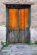 Stepping stones lead to an old wood door with faded orange stain and blue green trim, in Kastraki, Meteora, Greece.