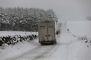 A delivery van drives through a snowy landscape on 14th of January 2021 in Stow, Scottish Borders, United Kingdom. The snow has been falling all night and morning and the landscape is covered in the first real snow of the year. The van is making its way down the Lauder Road towards the village Stow.