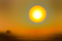 Hay Field @ Sunrise: This photograph reveals a surrealistic scene depicting the sun as a ball of fire, attempting to break through a thick fog, suspended over a hay field, Surrey British Columbia Canada.