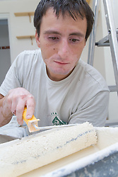 Bulgarian painter and decorator applying paint onto roller from paint tray,
