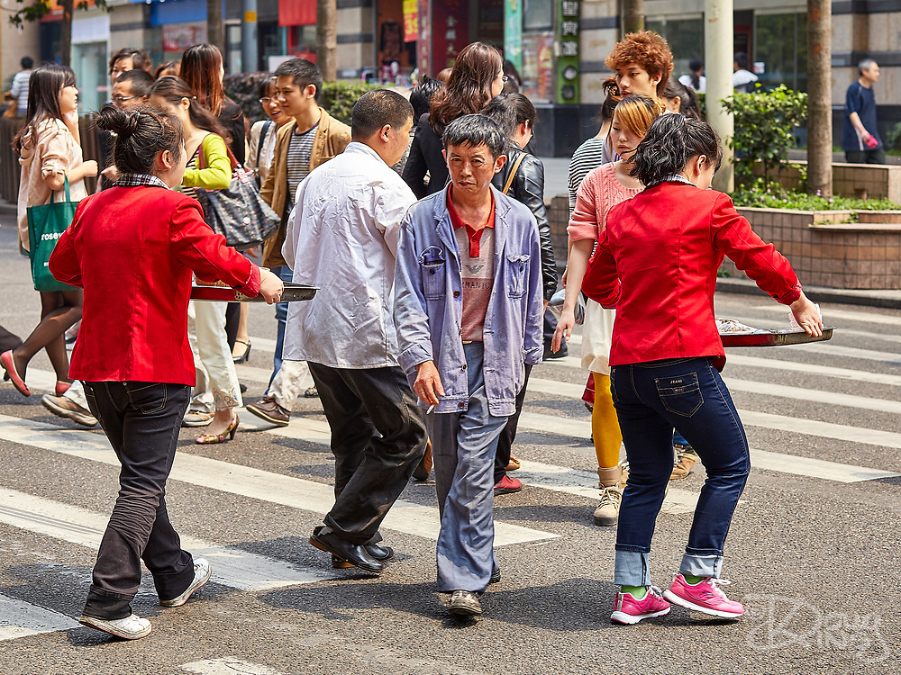 People weave between each other on a pedestrian crossing in downtown Chongqing