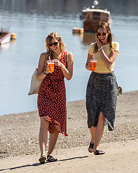 © Licensed to London News Pictures. 07/08/2020. London, UK. Two young women enjoy a cooling beer in the sunshine next to the River Thames at Putney Embankment in South West London as temperatures are expected to reach to 35c today. Thousands of sun seekers have flocked to parks, rivers and the south coast as temperatures soar with beaches and roads becoming jammed with holidaymakers. The heat is set to continue for the rest of the week with temperatures expected in the high 20s. Photo credit: Alex Lentati/LNP