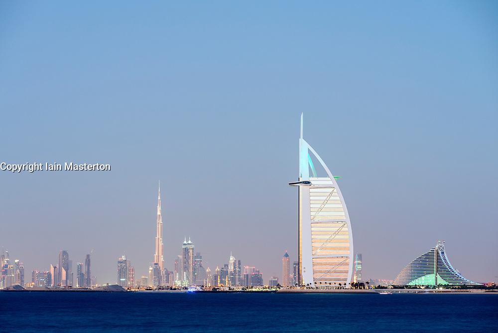 Night skyline across sea to luxury Burj al Arab hotel and city of Dubai with Burj Khalifa tower in distance in United Arab Emirates