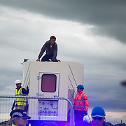 Anti-fracking  activists and protesters outside the gates of Quadrilla's fracking site June 31st, Lancashire, United Kingdom. An activists got on the truck which kept moving and took hin inside the Quadrilla perimeter. The struggle against fracking in Lancashire has been going on for years. The fracking company Quadrilla is finally ready to bring in a drill tower to start drilling and anti-frackinhg activists are waiting in front of the gates to block the equipment getting in.