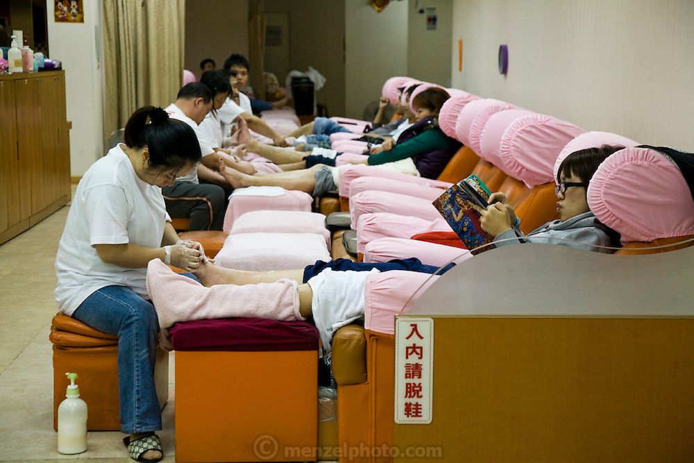 A woman relaxes and reads a magazine as a massage therapist attends to her foot at a foot massage spa in Taipei, Taiwan.