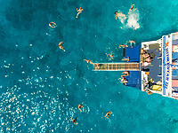 ITHAKI - GREECE, AUGUST 9 2018: Aerial view of people on ferry diving into sea, Ithaki island, Greece.