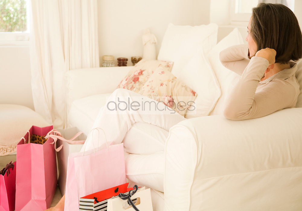 Woman sitting in living room with shopping bags