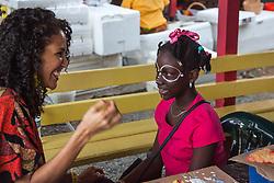 Tanama Colibri paints the face of Yvelle Macfarlane.  20th Annual Bordeaux Farmers Rastafari Agricultural & Cultural Vegan Food Fair.  Bordeaux Farmers Market.  St. Thomas, USVI.  14 January 2017.  © Aisha-Zakiya Boyd