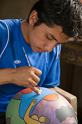 Central America, Nicaragua, Catarina (near Grenada).  Potter painting contemporary clay pottery.  Catarina is one of the Pueblas Blancas (white towns).