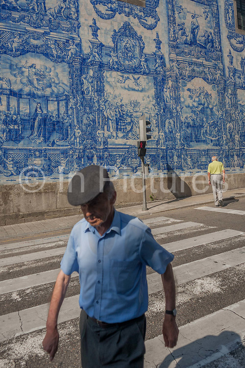 Elderly gentlemen crossing the Rua de Fernandes Tomas with Azulejo tiles on the exterior of Capela Das Almas, on 19th July, in Porto, Portugal. The Churchs magnificent panels depict scenes from the lives of various saints, including the death of St Francis and the martyrdom of St Catherine. Eduardo Leite painted the tiles in a classic 18th-century style, though they actually date back only to the early 20th century.