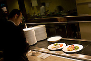 A Head Waiter is about to take finished dishes during service in the Vivre restaurant in Heathrow Airport's Sofitel.