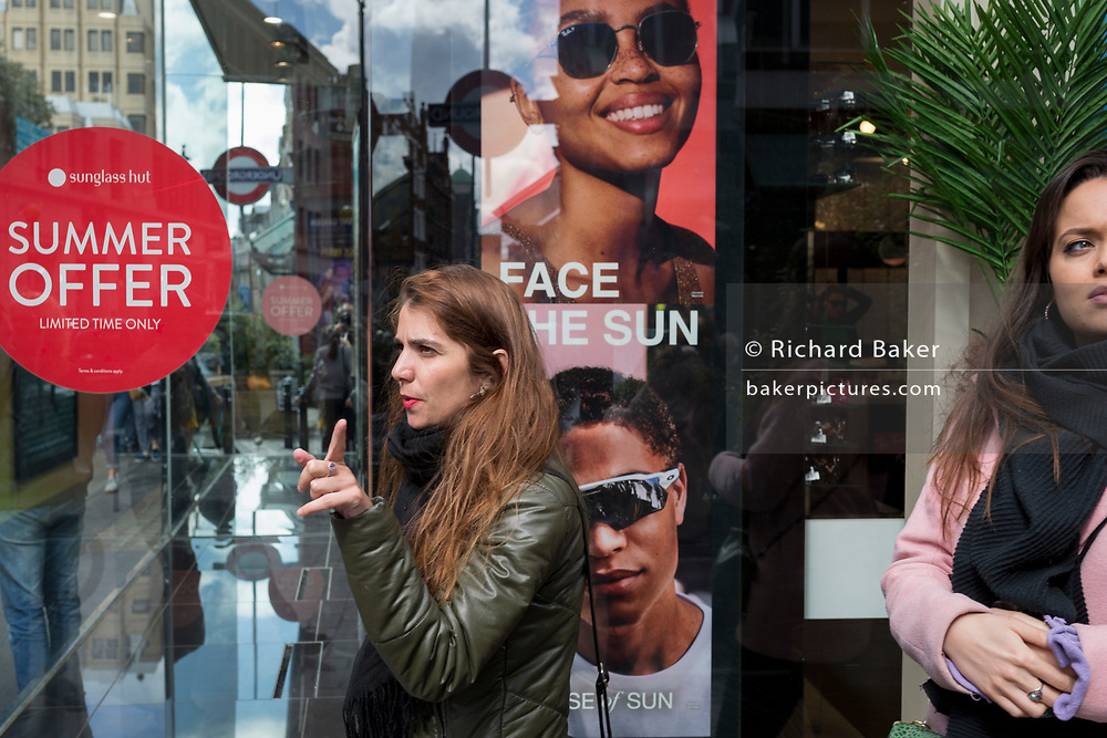 Women pass the window of the Sunglass Hut retailer in Covent Garden whose current slogan is 'Face the Sun', on 15th June 2019, in London, England.