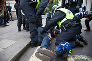 London, UK. Tuesday 11th June 2013. Injured protester being looked at by police during  demonstration against the upcoming G8 summit in central London, UK.