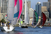 With their spinnaker sails up, taking advantage of an east wind, these sailboats, part of the Downtown Sailing Series first race, head for a turn buoy by the Great Wheel on the Seattle waterfront. <br />