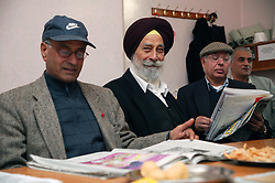 Members of the Sikh community relaxing and reading newspapers,