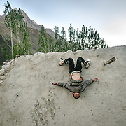 A boy plays on the wall of the family's mud house in Kermin village, in the Chapursan Valley.