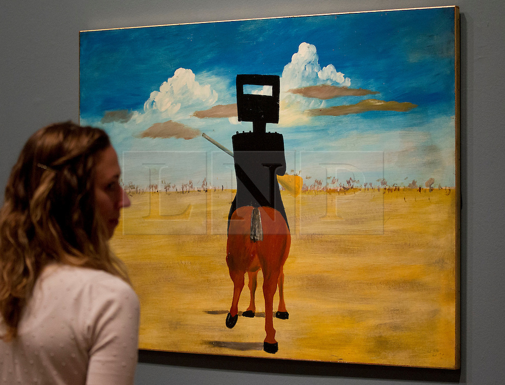 © Licensed to London News Pictures. 17/09/2013. London, UK. A member of gallery staff looks at 'Ned Kelly' (1946) by Australian artist Sidney Nolan at the press view for the Royal Academy of Arts latest exhibition 'Australia' in London today (17/09/2013). The exhibition, said to be the most significant survey of Australian art ever mounted in the UK, spans more than 200 years, from 1800 to the present, and runs from the 21st of September to the 8th of December 2013. Photo credit: Matt Cetti-Roberts/LNP
