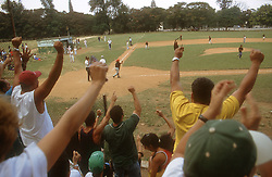 Crowd of spectators leaping to their feet in applause and encouragement at a baseball game for young people on the outskirts of Havana; Cuba,