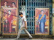 10 AUGUST 2016 - BANGKOK, THAILAND: A Thai man walks past portraits of Queen Sirikit of Thailand. Thais are preparing for the Queen's birthday. Queen Sirikit of Thailand, was born Mom Rajawongse Sirikit Kitiyakara on 12 August 1932. She married  Bhumibol Adulyadej, King of Thailand (Rama IX) in 1950. He is the longest serving monarch in the world and she is longest serving consort of a monarch. Her birthday, like the King's Birthday (which falls on Dec. 5),  is a national holiday in Thailand. Her birthday, August 12, is also celebrated as Mothers' Day in Thailand. Thais hang portraits of Queen Sirikit in their homes and fly her royal flag on her birthday.        PHOTO BY JACK KURTZ