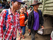 16 JUNE 2014 - POIPET, CAMBODIA:  Cambodian migrants walk among military trucks in Poipet, Cambodia, after fleeing Thailand Monday. More than 150,000 Cambodian migrant workers and their families have left Thailand since June 12. The exodus started when rumors circulated in the Cambodian migrant community that the Thai junta was going to crack down on undocumented workers. About 40,000 Cambodians were expected to return to Cambodia today. The mass exodus has stressed resources on both sides of the Thai/Cambodian border. The Cambodian town of Poipet has been over run with returning migrants. On the Thai side, in Aranyaprathet, the bus and train station has been flooded with Cambodians taking all of their possessions back to Cambodia.   PHOTO BY JACK KURTZ