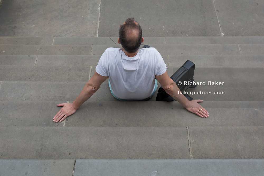 A man leans back on his hands on the steps outside Tate Britain on Millbank, on 4th August 2019, in London, England