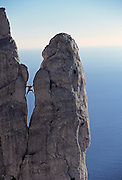 """A male rock climber """"chimneys"""" up the side of a rock tower in the Calanques, a rock climbing area near Cassis and Marseilles in the South of France."""