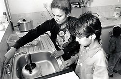 Boy helping his mother in the kitchen, Forest Fields, Nottingham UK 1990