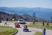 Visitors flock to see views from Waterrock Knob at Blue Ridge Parkway Milepost 451.2 in North Carolina, USA. Waterrock Knob (summit elevation 6292 feet) is the highest peak of the Plott Balsam Range, part of the Blue Ridge Mountains. This view looks west to the Qualla Boundary, the Eastern Cherokee Reservation, and Great Smoky Mountains. At upper left edge are the Unicoi Mountains (traversed by Cherohala Skyway). Local trees release hydrocarbons into the atmosphere and create a characteristic blue haze on pristine days as seen in this photo; but more often a white or gray haze caused by air pollution obscures distant views. The 469-mile Blue Ridge Parkway connects Shenandoah National Park (in Virginia) with the Great Smoky Mountains National Park in North Carolina. (The Smokies are a subrange of the Blue Ridge Mountains, all part of the Appalachian Mountains.)