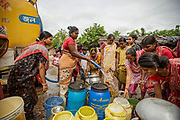 Once a day a large bowser delivers the district's only source of clean water. Women fill large plastic drums with water, which they will carry back to their homes. The water will provide all their families' water for cooking, cleaning and sanitation, Tangra slum, Dhipi, Kolkata, India